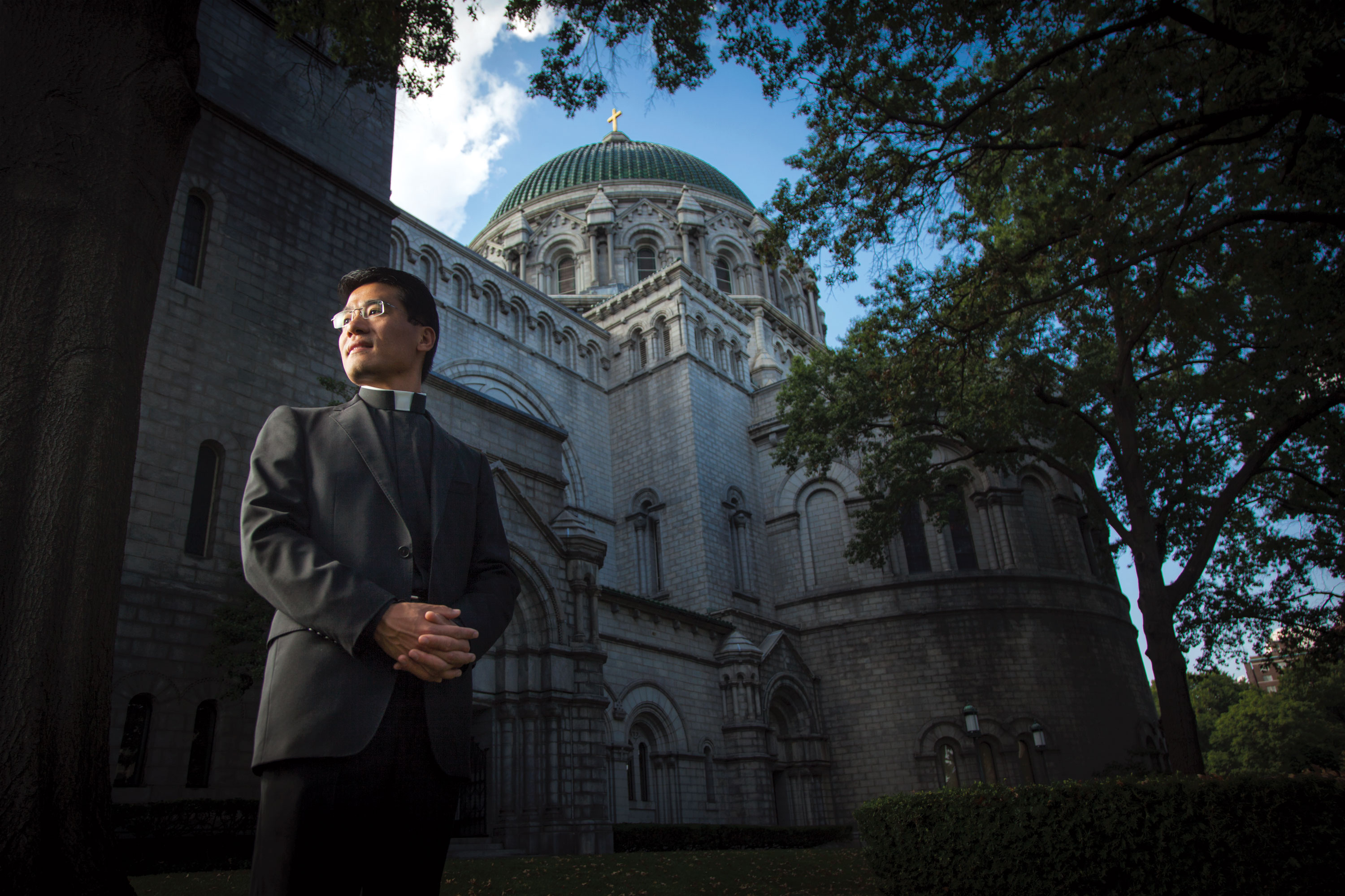 Father Xiu Hui Joseph Jiang stands in front of the Cathedral Basilica of Saint Louis. His first assignment after being ordained in 2010 was to serve as associate pastor at the cathedral, where he met the Maritain family. (Photo by Matt Marcinkowski)
